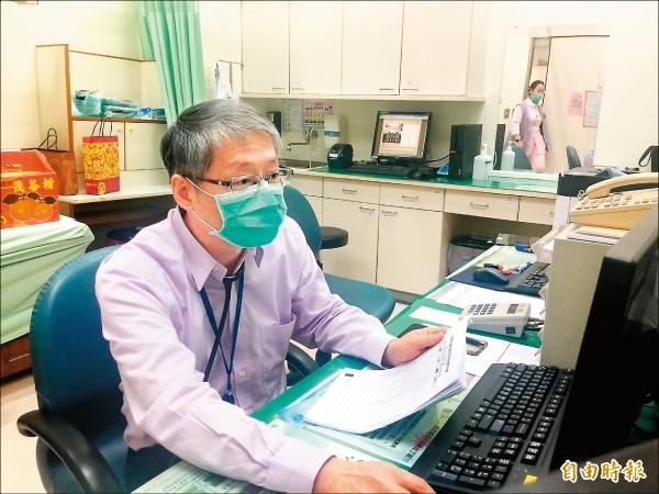 ▲許榮彬醫師檢視患者的血壓、心跳及體重紀錄表。(記者羅碧攝)