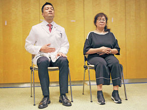 黃仰山教授(左)及馮女士(右)示範修習靜觀,馮女士指靜觀有助她放鬆入眠。(梁偉榮攝)