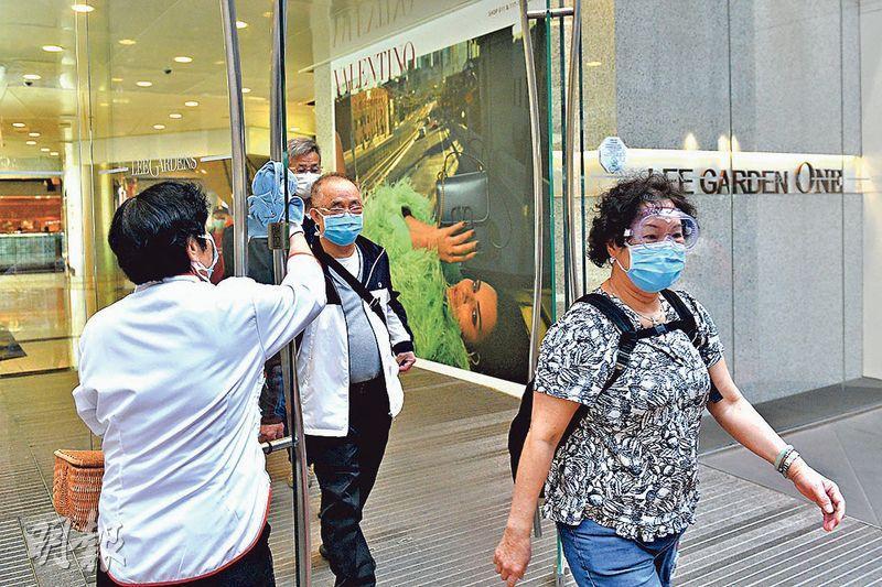 本港第114宗確診患者、41歲英籍男子,潛伏期內曾到銅鑼灣利園一期上班,昨午有清潔人員清潔大門,其間有市民出入時戴口罩及眼罩防疫。(林靄怡攝)